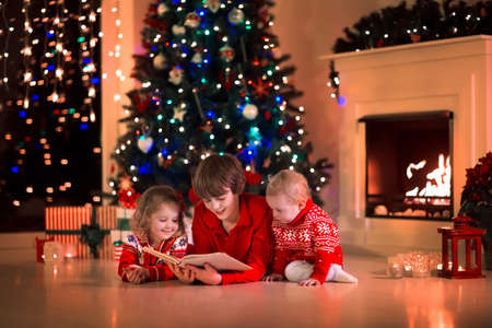 fireplace home: Children read a book and open gifts at fireplace on Christmas eve. Family with child celebrating Xmas. Decorated living room with tree, fire place, candles. Winter evening at home for parents and kids