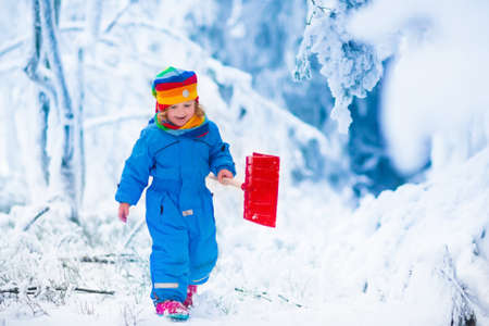yard: Little girl shoveling snow on home drive way. Beautiful snowy garden or front yard. Child with shovel playing outdoors in winter season. Family removing snow after blizzard. Kids play outside.