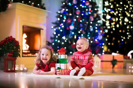 xmas baby: Family on Christmas eve at fireplace. Kids opening Xmas presents. Children under Christmas tree with gift boxes. Decorated living room with traditional fire place. Cozy warm winter evening at home. Stock Photo