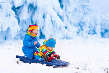 Meisje en jongen te genieten van een sledetocht. Kind sleeën. Peuter jongen rijden op een slee. De kinderen spelen buiten in de sneeuw. Kids slee in de Alpen bergen in de winter. Outdoor plezier voor familie kerstvakantie. Stockfoto