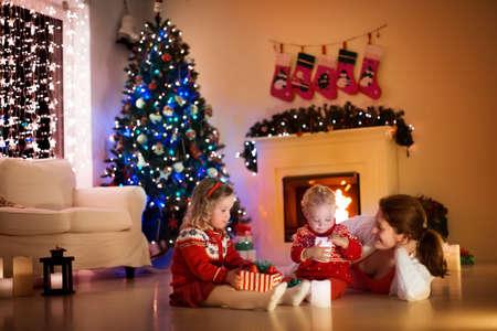 Ouders en kinderen ontspannen in de open haard op kerstavond. Gezin met kinderen vieren Kerstmis. Ingerichte woonkamer met boom, open haard en kaarsen. Winter avond thuis. Jongen en meisje openen presenteert Stockfoto