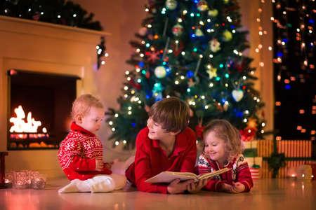 De kinderen lezen een boek en een open giften bij open haard op kerstavond. Gezin met kind vieren Kerstmis. Ingerichte woonkamer met boom, open haard, kaarsen. Winter avond thuis voor ouders en kinderen