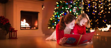 Mother and daughter read a book at fireplace on Christmas eve. Family with child celebrating Xmas. Decorated living room with tree, fire place and candles. Winter evening at home for parents and kids. Stock fotó