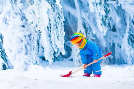 Meisje sneeuwschuiven op eigen oprit. Prachtige besneeuwde tuin of voortuin. Kind met schop spelen buiten in de winter seizoen. Familie verwijderen van sneeuw na sneeuwstorm. Kinderen buiten spelen.