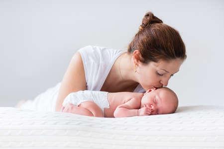 bebês: Matriz nova que abraça seu filho recém-nascido. Mamãe bebê de enfermagem. Mulher e menino recém-nascido relaxar em um quarto branco. Família em casa. Amor, confiança e conceito ternura. Roupa de cama e têxteis para o berçário.