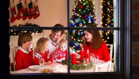 christmas dish: Big family with three children celebrating Christmas at home. Festive dinner at fireplace and Xmas tree. Parent and kids eating at fire place in decorated room. Child lighting advent wreath candle Stock Photo
