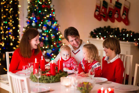 huge christmas tree: Big family with three children celebrating Christmas at home. Festive dinner at fireplace and Xmas tree. Parent and kids eating at fire place in decorated room. Child lighting advent wreath candle Stock Photo