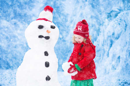 making fun: Funny little toddler girl in a red knitted Nordic hat and warm coat playing with a snow man. Kids play outdoors in winter. Children having fun at Christmas time. Child building snowman at Xmas.
