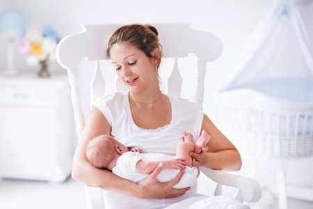 seni: Giovane madre che tiene il suo bambino appena nato. Mamma bambino di cura. Donna e nuovo ragazzo nato rilassarsi in una camera da letto bianco con sedia e blu culla a dondolo. Nursery interno. Madre allattamento al seno il bambino. Famiglia a casa Archivio Fotografico