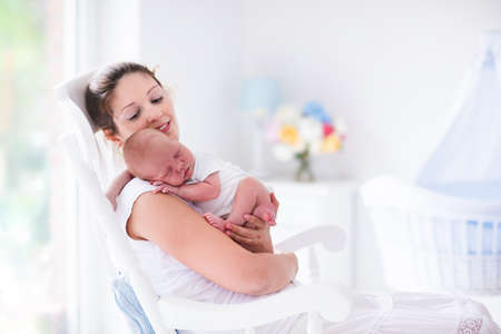 breastfeeding: Young mother holding her newborn child. Mom nursing baby. Woman and new born boy relax in a white bedroom with rocking chair and blue crib. Nursery interior. Mother breast feeding baby. Family at home
