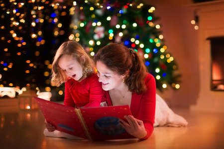 new year tree: Mother and daughter read a book at fireplace on Christmas eve. Family with child celebrating Xmas. Decorated living room with tree, fire place and candles. Winter evening at home for parents and kids. Stock Photo
