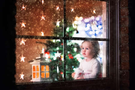 through the window: Little girl watching snow through window. Family with children on Christmas eve in decorated living room with tree and candles. Kids open Xmas presents. Cozy winter evening at home. View from outside. Stock Photo