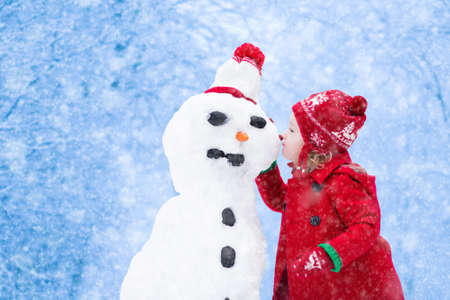play: Funny little toddler girl in a red knitted Nordic hat and warm coat playing with a snow man. Kids play outdoors in winter. Children having fun at Christmas time. Child building snowman at Xmas.