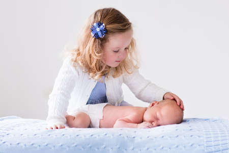 girl care: Little sister hugging her newborn brother. Toddler kid meeting new sibling. Cute girl and new born baby boy relax in a white bedroom. Family with children at home. Love, trust and tenderness concept.