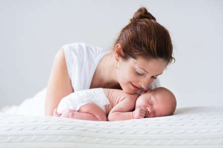 Young mother hugging her newborn child. Mom nursing baby. Woman and new born boy relax in a white bedroom. Family at home. Love, trust and tenderness concept. Bedding and textile for nursery. Standard-Bild