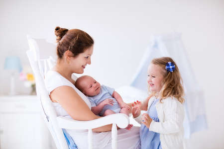 new born baby girl: Little sister hugging her newborn brother. Toddler kid meeting new sibling. Mother and new born baby boy relax in a white bedroom. Family with children at home. Love, trust and tenderness concept.