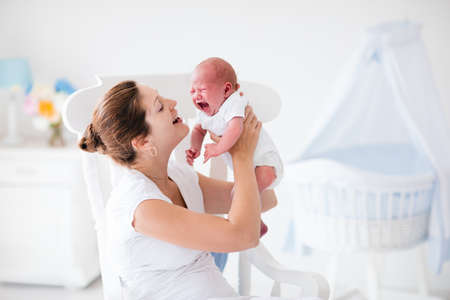 Une jeune mère tenant son enfant nouveau-né. Mère réconfortante pleurer bébé affamé. Femme et le nouveau garçon né détendre dans une chambre blanche avec chaise berçante et berceau bleu. Intérieur pépinière. Famille à la maison.