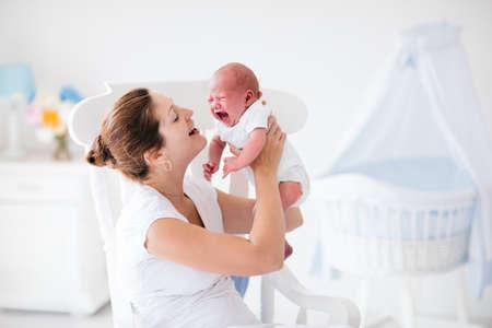 fille qui pleure: Une jeune mère tenant son enfant nouveau-né. Mère réconfortante pleurer bébé affamé. Femme et le nouveau garçon né détendre dans une chambre blanche avec chaise berçante et berceau bleu. Intérieur pépinière. Famille à la maison.