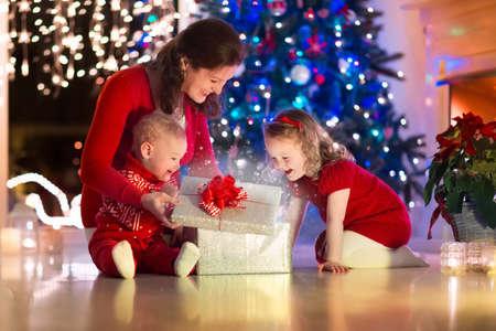 sorpresa: Familia en la víspera de Navidad en la chimenea. La madre y los niños pequeños de apertura de Navidad regalos. Los niños con cajas de regalo. Salón con chimenea tradicional y árbol decorado. Acogedor noche de invierno en casa.