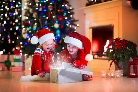 Familia en la víspera de Navidad en la chimenea. Niños de apertura de Navidad regalos. Los niños menores de árbol de Navidad con cajas de regalo. Sala de estar decorada con chimenea tradicional. Acogedor cálida noche de invierno en casa. Foto de archivo - 46880423