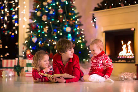 place for children: Children read a book and open gifts at fireplace on Christmas eve. Family with child celebrating Xmas. Decorated living room with tree, fire place, candles. Winter evening at home for parents and kids