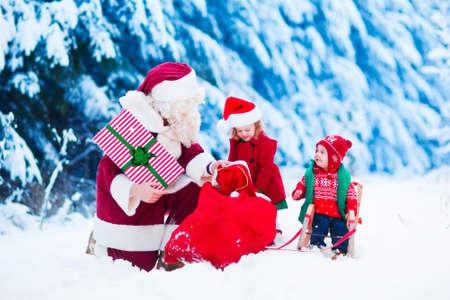 weihnachtsmann lustig: Weihnachtsmann und die Kinder �ffnen Geschenke im schneebedeckten Wald. Kinder und Vater im Sankt-Kost�m und Bart ge�ffnet Weihnachtsgeschenke. Kleines M�dchen hilft mit sack. Weihnachten, Schnee und Winterspa� f�r Familien. Lizenzfreie Bilder