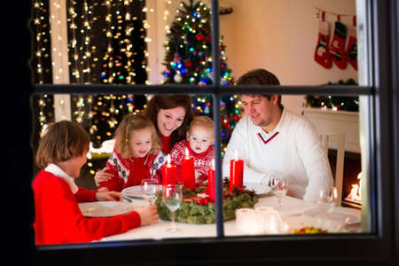 home lighting: Big family with three children celebrating Christmas at home. Festive dinner at fireplace and Xmas tree. Parent and kids eating at fire place in decorated room. Child lighting advent wreath candle Stock Photo