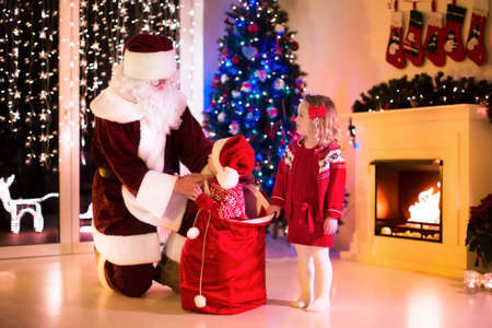 baby open present: Children and Santa Claus at fireplace on Christmas eve. Family celebrating Xmas. Decorated living room with tree, gifts, fire place, candles. Winter evening at home for parents and kids.