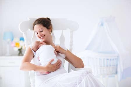 lactancia materna: Joven madre sosteniendo a su hijo recién nacido. Bebé lactante mamá. La mujer y el muchacho recién nacido se relajan en una habitación blanca con mecedora y azul cuna. Vivero interior. Madre bebé la lactancia materna. Familia en el país