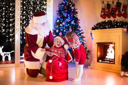 place for children: Ni�os y Santa Claus en la chimenea en la v�spera de Navidad. Familia que celebra Navidad. Sala de estar decorada con el �rbol, regalos, chimenea, velas. Noche de invierno en el hogar para los padres y ni�os.