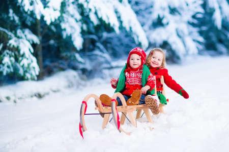 trineo: Niña y niño disfrutar de un paseo en trineo. Trineo Niño. Niño del niño montado en un trineo. Los niños juegan al aire libre en la nieve. Niños trineo en montañas de los Alpes en invierno. Diversión al aire libre para la familia las vacaciones de Navidad. Foto de archivo