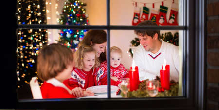 fireplace family: Big family with three children celebrating Christmas at home. Festive dinner at fireplace and Xmas tree. Parent and kids eating at fire place in decorated room. Child lighting advent wreath candle Stock Photo