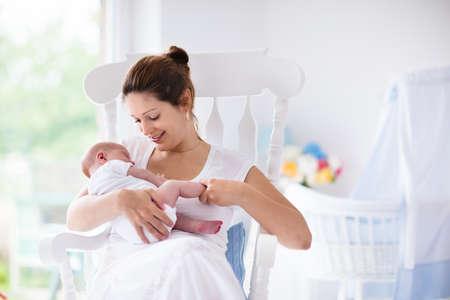 amamantando: Joven madre sosteniendo a su hijo recién nacido. Bebé lactante mamá. La mujer y el muchacho recién nacido se relajan en una habitación blanca con mecedora y azul cuna. Vivero interior. Madre bebé la lactancia materna. Familia en el país