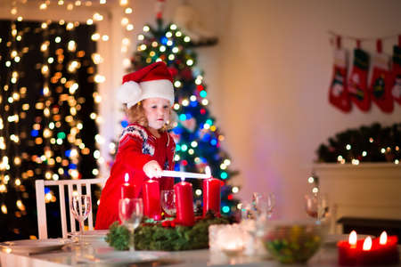 tree decorations: Christmas dinner at home. Child lighting a candle on advent wreath on Xmas eve. Decorated living room with fireplace and tree. Winter evening at fire place for family with kids. Children celebrating.