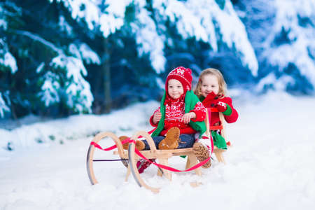 christmas fun: Little girl and boy enjoy a sleigh ride. Child sledding. Toddler kid riding a sledge. Children play outdoors in snow. Kids sled in Alps mountains in winter. Outdoor fun for family Christmas vacation.