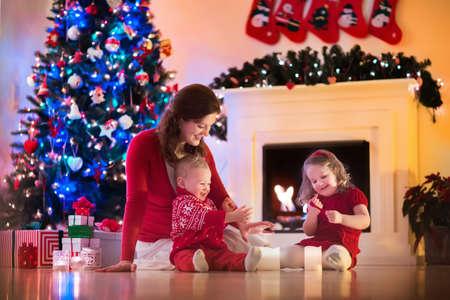 camino natale: Famiglia alla vigilia di Natale al camino. Madre e bambini piccoli di apertura regali di Natale. I bambini con confezioni regalo. Soggiorno con camino tradizionale e albero decorato. Cozy sera d'inverno a casa.