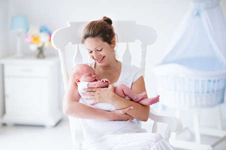 Young mother holding her newborn child. Mom nursing baby. Woman and new born boy relax in a white bedroom with rocking chair and blue crib. Nursery interior. Mother breast feeding baby. Family at home