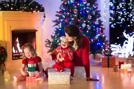present: Family on Christmas eve at fireplace. Mother and little kids opening Xmas presents. Children with gift boxes. Living room with traditional fire place and decorated tree. Cozy winter evening at home.