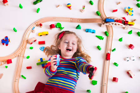 educational: Child playing with wooden train, rails and cars. Toy railroad for kids. Educational toys for preschool and kindergarten children. Little girl at daycare. View from above, kid playing on the floor. Stock Photo