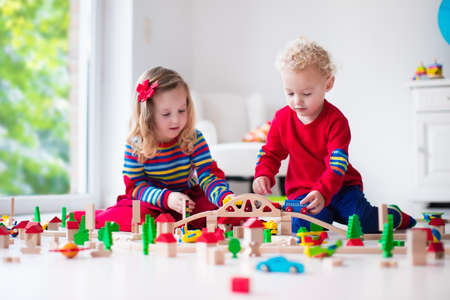 wood railroad: Children playing with wooden train. Toddler kid and baby play with blocks, trains and cars. Educational toys for preschool and kindergarten child. Boy and girl build toy railroad at home or daycare.