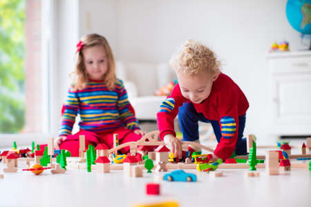niños jugando: Niños jugando con el tren de madera. Niño niño y el bebé juegan con bloques, trenes y coches. Juguetes educativos para preescolar y jardín de infantes menores. El muchacho y la estructura de la muchacha ferrocarril del juguete en casa o en la guardería.