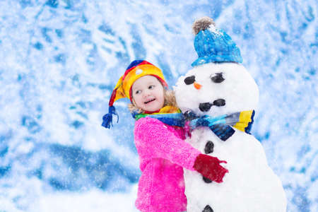 Funny little toddler girl in a colorful hat and warm coat playing with a snow man. Kids play outdoors in winter. Children having fun at Christmas time. Child building snowman at Xmas.