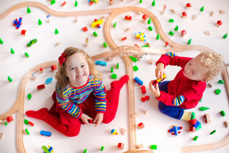 Children playing with wooden train. Toy railroad. Toddler kid and baby play with blocks, trains and cars. Educational toys for preschool and kindergarten child. View from above, kids on the floor.
