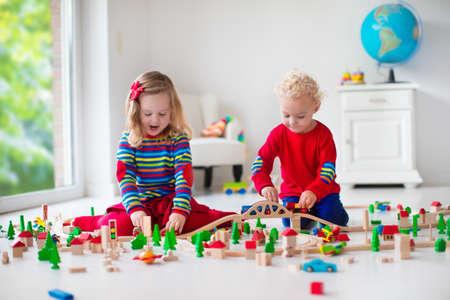 niñas jugando: Niños jugando con el tren de madera. Niño niño y el bebé juegan con bloques, trenes y coches. Juguetes educativos para preescolar y jardín de infantes menores. El muchacho y la estructura de la muchacha ferrocarril del juguete en casa o en la guardería.