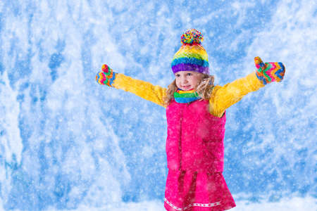 winter fashion: Little girl in pink jacket and colorful knitted hat catching snowflakes in winter park. Kids play outdoor in snowy forest. Children catch snow flakes. Toddler kid playing outside in snow storm. Stock Photo