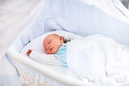 nacimiento: Bebé recién nacido en la cama. Niño recién nacido durmiendo bajo una manta de punto blanco. Duermen los niños. Ropa de cama para los niños. Siesta infantil en la cama. Niño sano poco después del nacimiento. Cable tejer textil. Foto de archivo