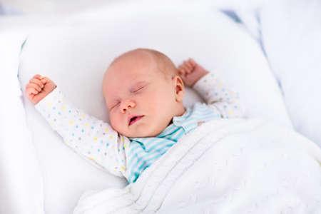 乳幼児: ベッドで生まれたばかりの赤ちゃんの男の子。新しい生まれの子は、白いニット毛布の下で眠っています。子供は眠る。子供のための寝具。幼児ベッドで昼寝しま