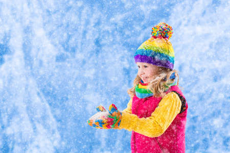 outdoor outside: Little girl in pink jacket and colorful knitted hat catching snowflakes in winter park. Kids play outdoor in snowy forest. Children catch snow flakes. Toddler kid playing outside in snow storm. Stock Photo