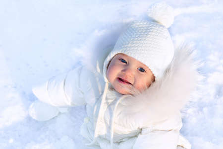 Funny little baby girl in a white knitted hat and warm white coat playing with snow. Kids play outdoors in winter. Children having fun at Christmas time. Child and infant cold weather clothing. Stock Photo