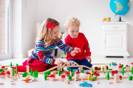 indoors: Children playing with wooden train. Toddler kid and baby play with blocks, trains and cars. Educational toys for preschool and kindergarten child. Boy and girl build toy railroad at home or daycare.